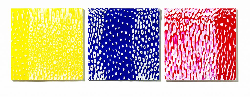 Three square glass panels in opaque red, yellow and blue with white patterns